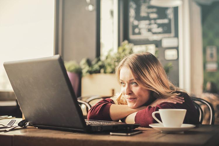 Junge Frau hat ihre Arme auf dem Tisch verschränkt und ihr Kinn darauf gelegt. Sie schaut auf einen Computer.