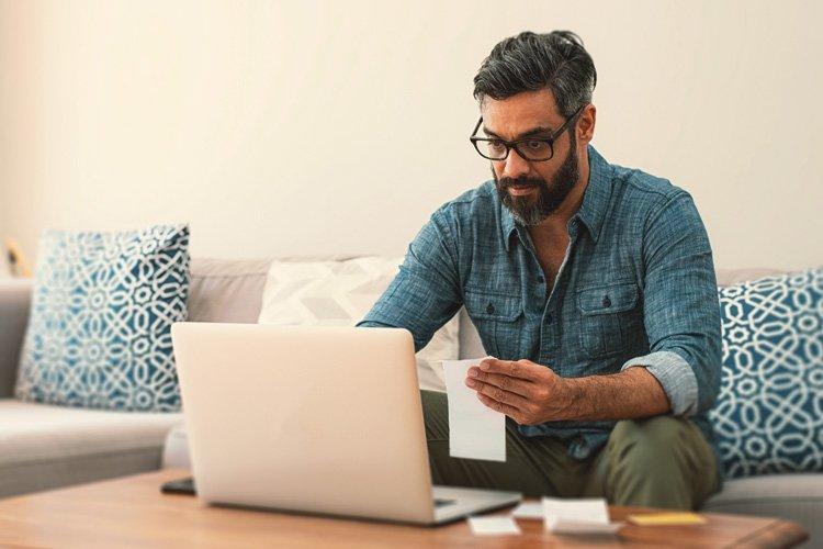 Mann sitzt vor Computer und kontrolliert dabei Rechnungen.
